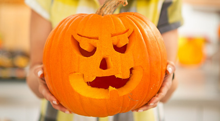 frightful: Frightful Treats on the way. Smiling modern housewife in the Halloween decorated kitchen showing big pumpkin Jack-O-Lantern. Closeup