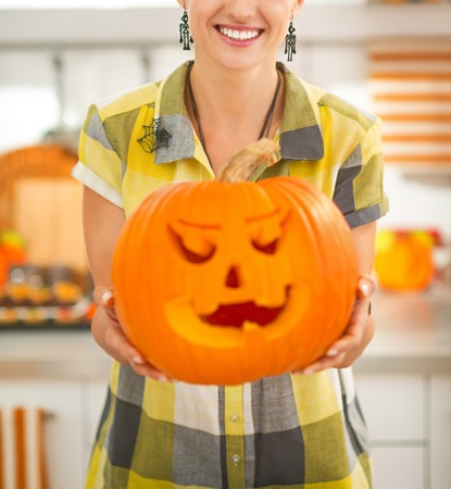 Frightful Treats on the way. Closeup on happy modern housewife in the Halloween decorated kitchen showing big pumpkin Jack-O-Lantern