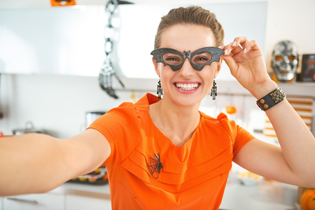 frightful: Frightful Treats all the way. smiling young woman in party bat glasses in the Halloween decorated kitchen taking selfie