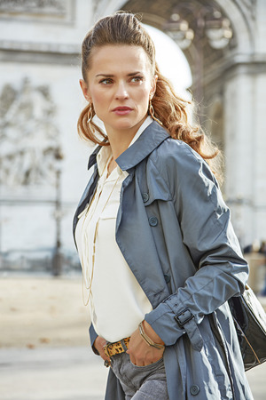 trench: Stylish autumn in Paris. elegant fashion-monger in trench coat near Arc de Triomphe in Paris, France looking aside