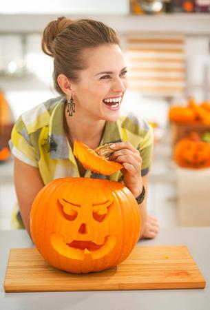 frightful: Frightful Treats on the way. happy modern housewife in the Halloween decorated kitchen with a big orange pumpkin Jack-O-Lantern Stock Photo