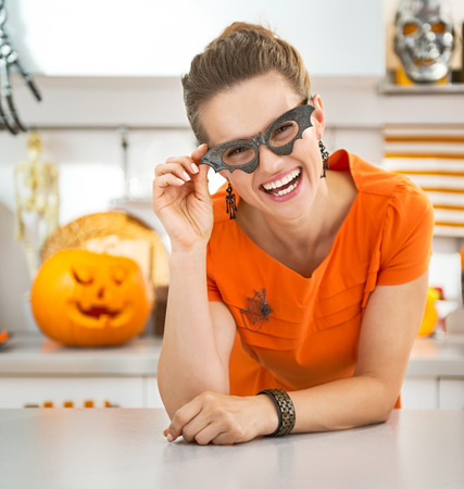 frightful: Frightful Treats all the way. Portrait of smiling young woman in party bat glasses in the Halloween decorated kitchen