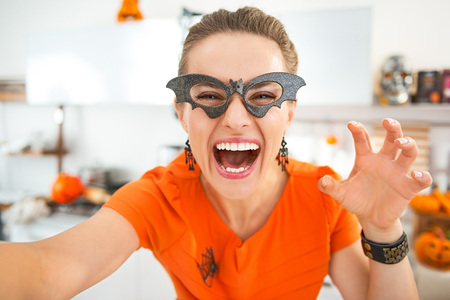Frightful Treats all the way. happy young woman in party bat glasses in the Halloween decorated kitchen taking selfie and frightening