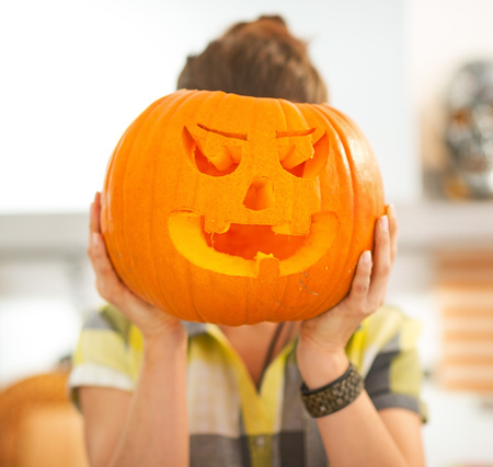 frightful: Frightful Treats on the way. Portrait of housewife in the Halloween decorated kitchen holding a big orange pumpkin Jack-O-Lantern in front of head