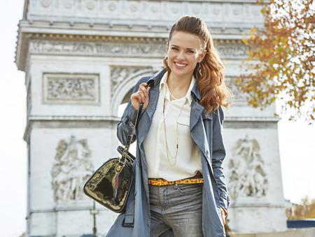 otoño con estilo en París. Retrato de la mujer elegante joven feliz en gabardina en París, Francia