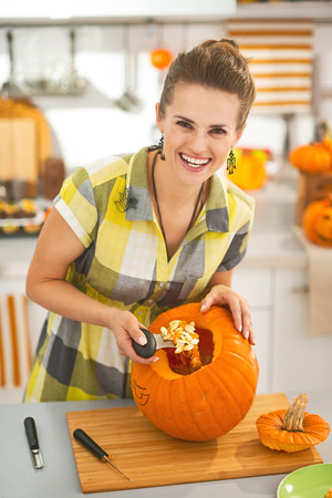 frightful: Frightful Treats on the way. Portrait of happy modern housewife in the Halloween decorated kitchen prepare big orange pumpkin for carving