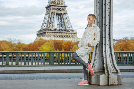 Year round fit & hip in Paris. Full length portrait of young healthy woman on Pont de Bir-Hakeim bridge in Paris looking into the distance Stock Photo