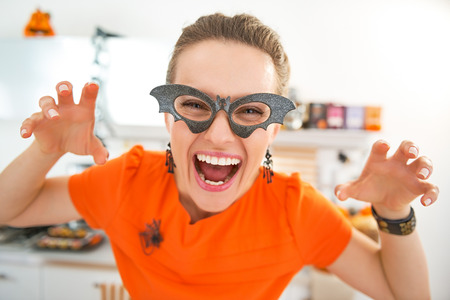 Frightful Treats all the way. smiling young woman in party bat glasses in the Halloween decorated kitchen frightening Stock Photo