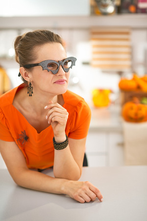 frightful: Frightful Treats all the way. Portrait of young woman in party bat glasses in the Halloween decorated kitchen looking aside