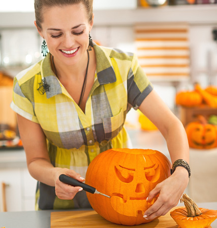 frightful: Frightful Treats on the way. happy young housewife in the Halloween decorated kitchen carving a big orange pumpkin Jack-O-Lantern