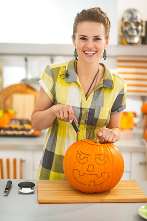 frightful: Frightful Treats on the way. happy young woman in the Halloween decorated kitchen carving a big orange pumpkin Jack-O-Lantern