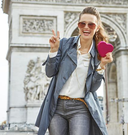 Elegante día de San Valentín en París. Retrato de feliz joven fashion-monger en gabardina en París, Francia mostrando caja de chocolates en forma de corazón rojo