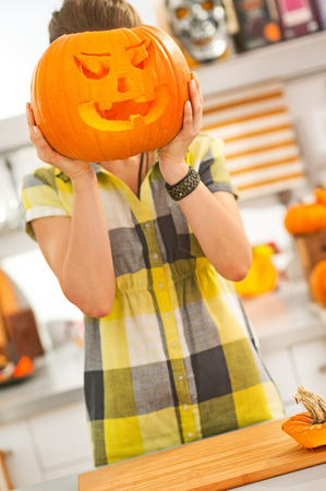 frightful: Frightful Treats on the way. young woman in the Halloween decorated kitchen holding a big orange pumpkin Jack-O-Lantern in front of head Stock Photo