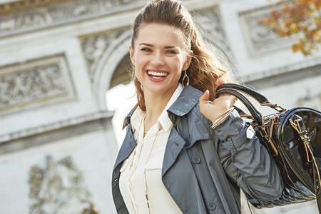 Stylish autumn in Paris. smiling young elegant woman in trench coat near Arc de Triomphe in Paris, France Stock Photo