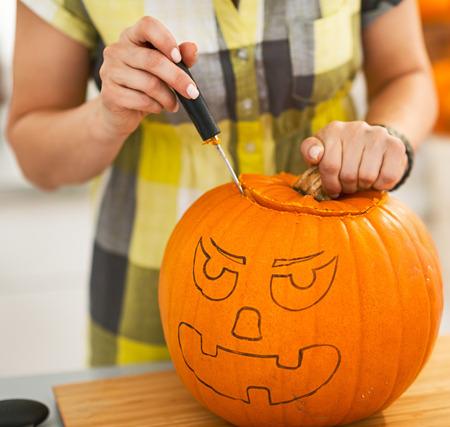 frightful: Frightful Treats on the way. Closeup on housewife in the Halloween decorated kitchen carving a big orange pumpkin Jack-O-Lantern