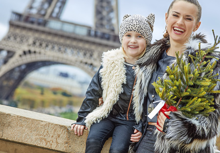 The Party Season in Paris. Portrait of happy modern mother and daughter with Christmas tree in the front of Eiffel tower in Paris, France