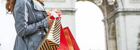 Stylish Christmas in Paris. Closeup on happy young woman in sunglasses with shopping bags and Christmas present near Arc de Triomphe in Paris, France Stock Photo