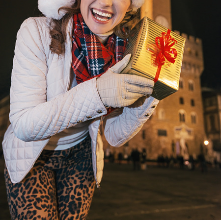 Trip full of inspiration at Christmas time in Florence. Closeup on happy modern woman in the front of Palazzo Vecchio in Florence, Italy showing Christmas present box