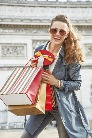champs elysees: Stylish Christmas in Paris. Portrait of smiling trendy woman with shopping bags and Christmas present box in Paris, France Stock Photo
