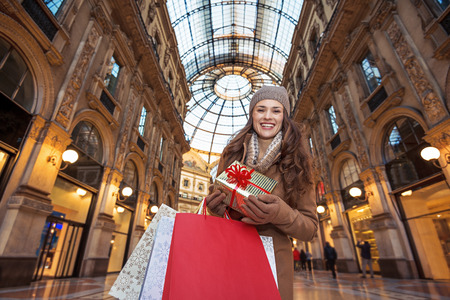 On a huge Christmas sales in Italian fashion capital. Portrait of happy young tourist woman with Christmas gift and shopping bags in Milan, Italy