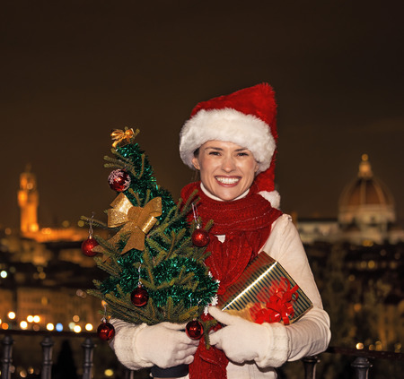 michelangelo: Trip full of inspiration at Christmas time in Florence. Portrait of smiling young woman in Christmas hat at Piazzale Michelangelo in Florence, Italy with Christmas tree and gift