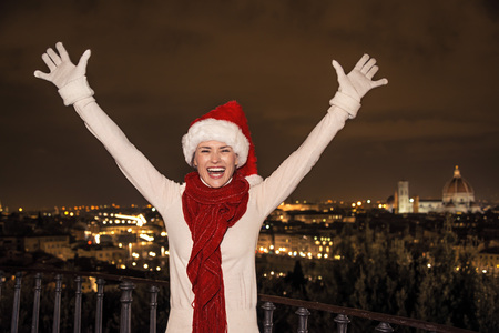 rejoicing: Trip full of inspiration at Christmas time in Florence. smiling young woman in Christmas hat at Piazzale Michelangelo in Florence, Italy rejoicing