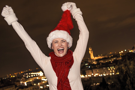 rejoicing: Trip full of inspiration at Christmas time in Florence. cheerful young woman in Christmas hat in the front of panoramic view of Florence rejoicing