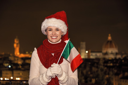 michelangelo: Trip full of inspiration at Christmas time in Florence. Portrait of smiling young woman in Christmas hat in Florence, Italy with Italian flag