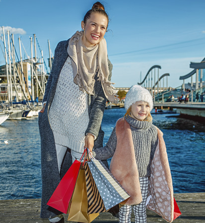 in Barcelona for a perfect present. Full length portrait of happy trendy mother and child with shopping bags in Barcelona, Spain having fun time