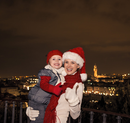 mam: Trip full of inspiration at Christmas time in Florence. Portrait of smiling young mother and daughter travellers in Christmas hats in the front of panoramic view of Florence showing thumbs up