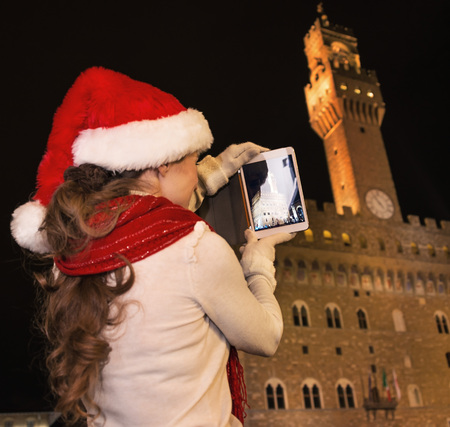 Trip full of inspiration at Christmas time in Florence. Seen from behind young tourist woman in Christmas hat against Palazzo Vecchio in Florence, Italy taking photo with tablet PC Stock Photo