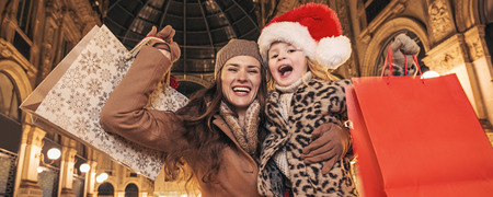 rejoicing: On a huge Christmas sales in Italian fashion capital. Portrait of happy young mother and daughter travellers in Galleria Vittorio Emanuele II in Milan, Italy with shopping bags rejoicing