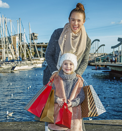 in Barcelona for a perfect present. Full length portrait of happy young mother and daughter with shopping bags in Barcelona, Spain standing on embankment