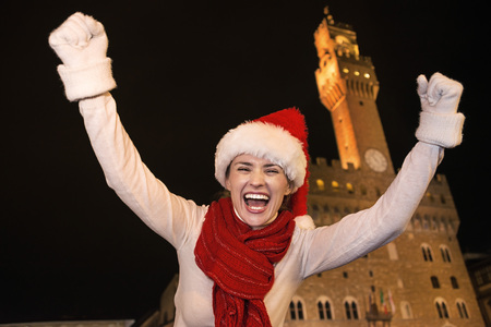 rejoicing: Trip full of inspiration at Christmas time in Florence. Portrait of happy young woman in Christmas hat in the front of Palazzo Vecchio in Florence, Italy rejoicing