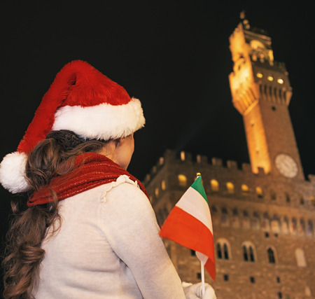 Trip full of inspiration at Christmas time in Florence. Seen from behind modern tourist woman in Christmas hat in the front of Palazzo Vecchio in Florence, Italy with Italian flag