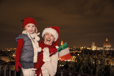 mam: Trip full of inspiration at Christmas time in Florence. smiling young mother and daughter travellers in Christmas hats at Piazzale Michelangelo in Florence, Italy with Italian flag