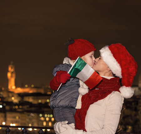 mam: Trip full of inspiration at Christmas time in Florence. smiling young mother and child travellers in Christmas hats with Italian flag in Florence, Italy kissing