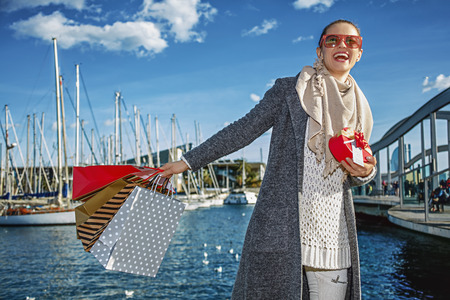 in Barcelona for a perfect present. cheerful young woman with shopping bags and Christmas present box in Barcelona, Spain looking into the distance Stock Photo