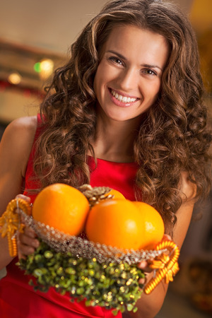 Portrait of happy young housewife showing plate of oranges
