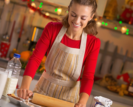 Happy young housewife rolling pin dough in christmas decorated kitchen Stock Photo