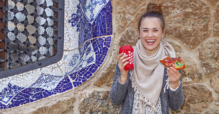spanish architecture: Winter wonderland in Barcelona at Christmas. Full length portrait of smiling elegant tourist woman with a cup of hot beverage and a piece of traditional king cake at Guell Park in Barcelona, Spain