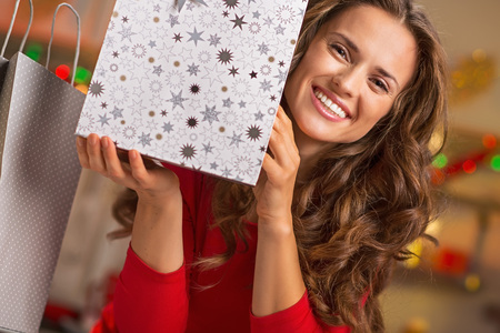 christmas shopping bag: Smiling young woman showing christmas shopping bag Stock Photo