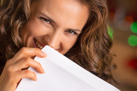 woman hiding: Smiling young woman hiding behind envelope Stock Photo
