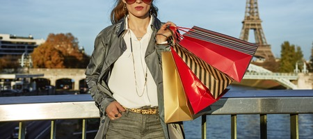 Get your bags ready for the Paris autumn sales. Closeup on young trendy woman in trench coat with shopping bags in Paris, France Stock Photo