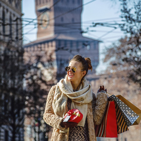 sforza: Rediscovering things everybody love in Milan. happy young woman with shopping bags and Christmas gift near Sforza Castle in Milan, Italy looking into the distance