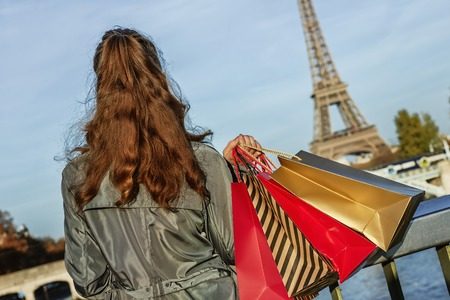 Get your bags ready for the Paris autumn sales. Seen from behind young elegant woman in sunglasses with shopping bags looking on Eiffel tower Stock Photo