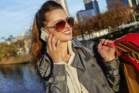 Get your bags ready for the Paris autumn sales. happy young elegant woman in sunglasses with shopping bags looking aside and speaking on a cell phone in Paris, France Stock Photo