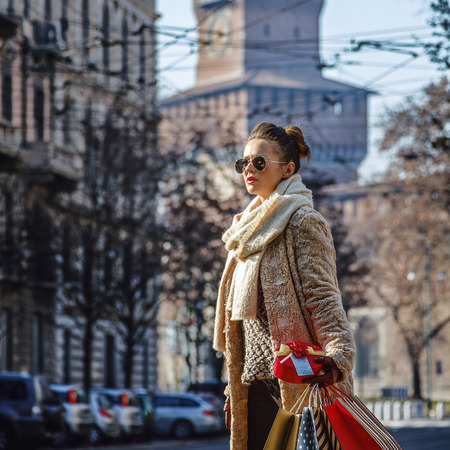 sforza: Rediscovering things everybody love in Milan. young tourist woman with shopping bags and Christmas gift near Sforza Castle in Milan, Italy looking into the distance and walking