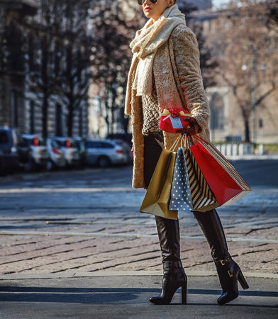 sforza: Rediscovering things everybody love in Milan. Closeup on young traveller woman with shopping bags and Christmas gift in Milan, Italy walking