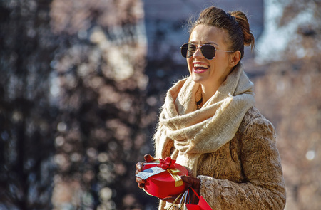 sforza: Rediscovering things everybody love in Milan. smiling trendy traveller woman with shopping bags and Christmas gift in Milan, Italy looking into the distance Stock Photo